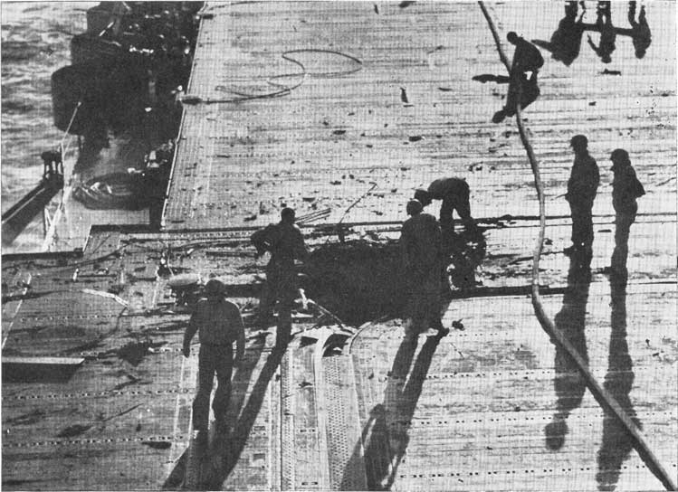 Figure 0-A. Bomb hole in the flight deck. Rapid covering of such holes is an important function of repair personnel.